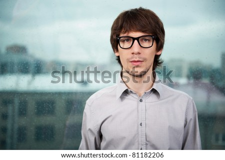 Closeup of a young smiling business man standing against big window with rain drops. City view.