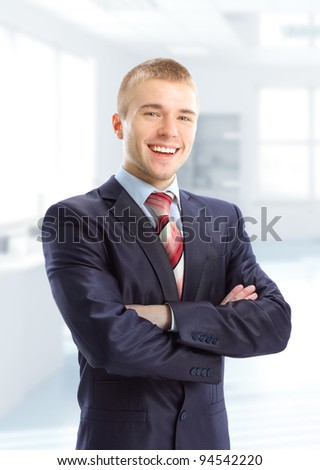 Closeup of a young smiling business man standing in his modern business office