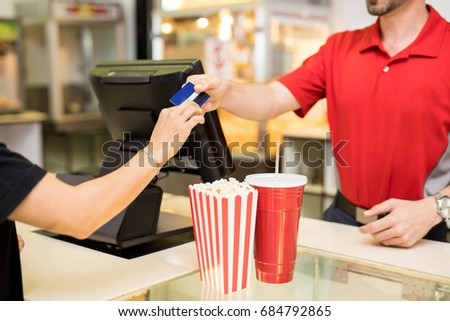 Closeup of a young woman handing over her credit card to pay for some snacks at the concession stand in a movie theater Сток-фото ©