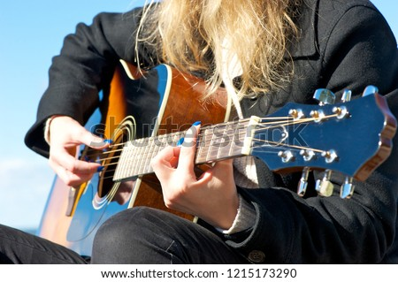 Closeup of a young woman's hand on an acoustic guitar; black clothes, blue nail polish.  #1215173290