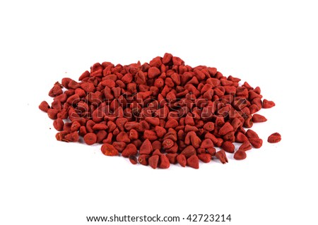 Closeup of achiote seeds over white background. Achiote is an herb, its seeds are used in cooking and gives a reddish color to the food.