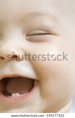 Closeup of adorable baby boy laughing with eyes closed