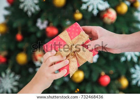 Closeup of adult female hand and small hand of child holding Christmas present in red wrapping paper. Mother and son or daughter exchanging presents on holiday. Blurry decorated tree in background.  #732468436
