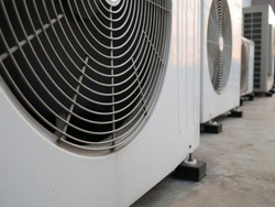 closeup of air conditioner compressor outside building.