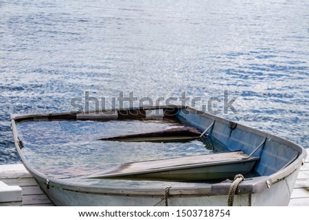 Closeup of aluminum rowboat almost full of rainwater on dock by lake, for concepts of adversity and excess, capacity, usability