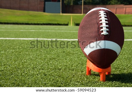 Closeup of American football on tee with goal post in background