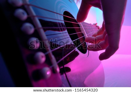 Closeup of an acoustic guitar played by a girl