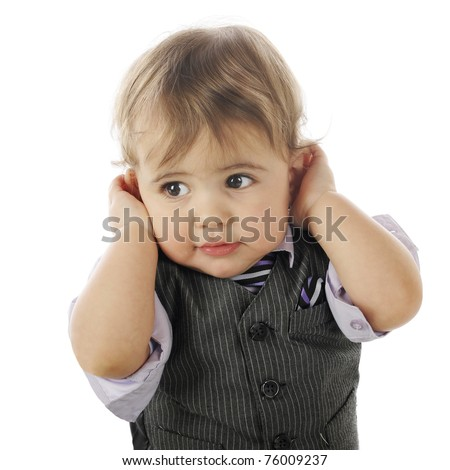Closeup of an adorable, dressed-up baby boy holding his hands over his ears.  Isolated on white.