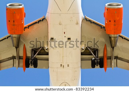 Closeup of an airplane with landing gear open view from below