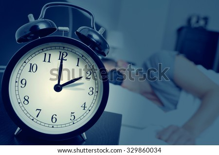 closeup of an alarm clock on a nightstand adjusting backward one hour at the end of the summer time, while a young man sleeps in bed #329860034
