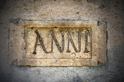 Closeup of an ancient Roman stone plaque with the text in Latin language Anni (Years in English language). Ostia Antica, near Rome, Latium, Italy, Europe.