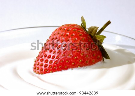 Closeup of an appetizing strawberry in cream