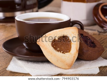 Closeup of an apricot filled hamantash cookie and cup of coffee #794903176