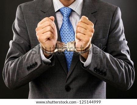 Closeup  of an arrested man with  handcuffs on grey