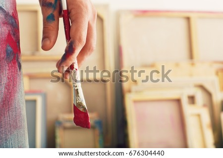 Closeup of an artist holding paintbrush #676304440