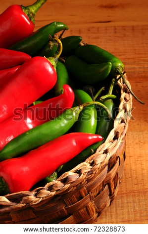 Closeup of an assortment of Peppers and Chilies in a wicker basket on a rustic wooden surface. Vertical Format.