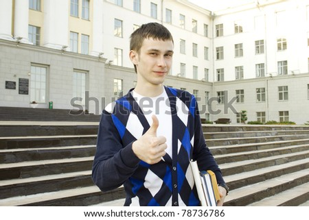 Closeup of an attractive male student on campus sits on the stairs with books. Thumbs up