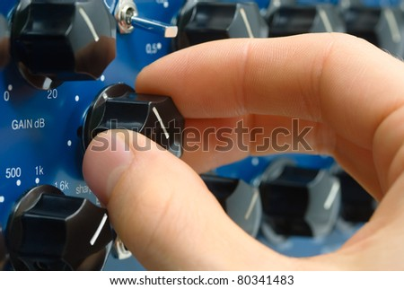 Closeup of an audio engineer's hand fine-tuning the sound on a knob