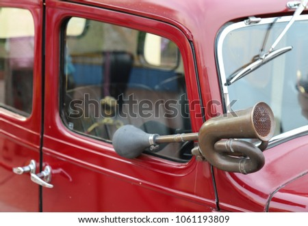 Closeup of an classic old brass hooter or a horn of vintage red car. #1061193809