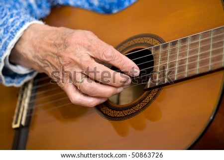 Closeup of an elderly woman playing the guitar.