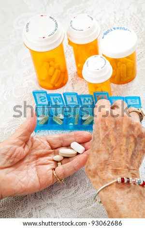 Closeup of an elderly woman's hands sorting her medication for the week.
