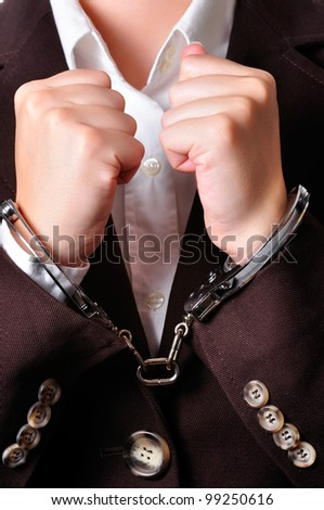 Closeup of an handcuffed businessperson in a brown suit