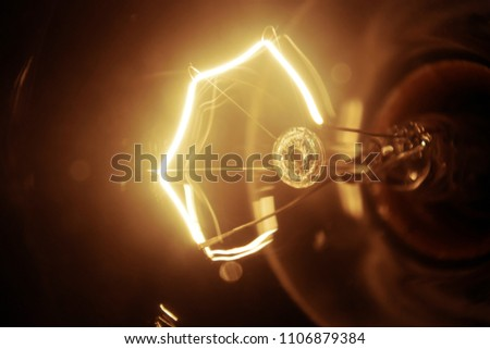 Closeup of an incandescent filament, glowing gold.