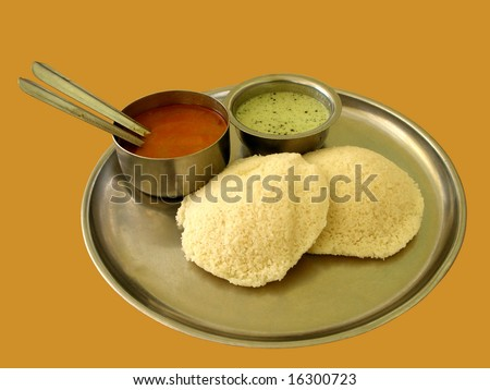 Closeup of an indian breakfast known as idly, which is cooked in steam and is served with chutney and curry.  Idly is a zero-cholesterol, healthy breakfast.