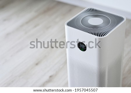 Closeup of an indoor Air purifier in the room is very safe and clean to breathe while dust air pollution situation outside is really bad. protect PM 2.5 dust and air pollution concept. Air purifier.