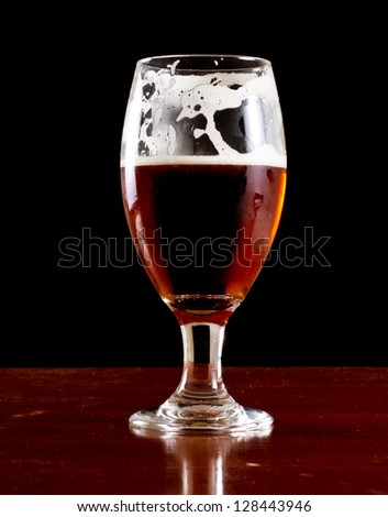 closeup of an irish red ale served on a bar isolated on a black background