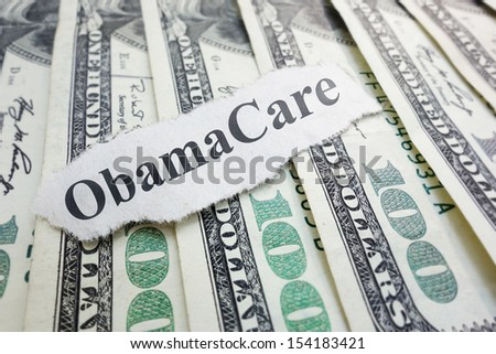 Closeup of an Obamacare newspaper headline on cash