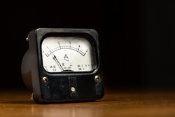 Closeup of an old black analog ampere meter on a wooden table
