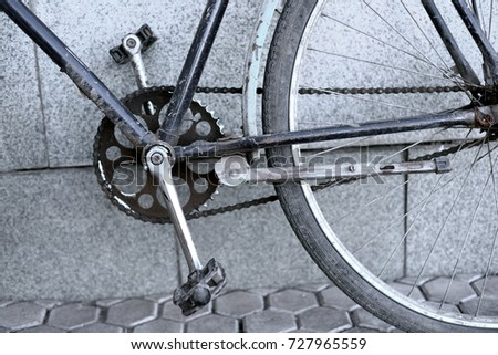 Stock Photo Closeup of an old blue vintage retro bicycle with pedals and chain cog against a concrete background