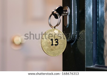 Closeup of an old keyhole of room number 13 with key on a wooden antique door.Concept photo of good or bed luck.