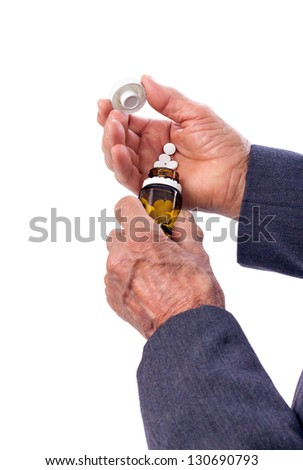 Closeup of an old man's hands with pills. White background