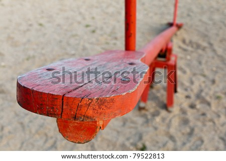 Closeup of an old red wooden seesaw playground on sand