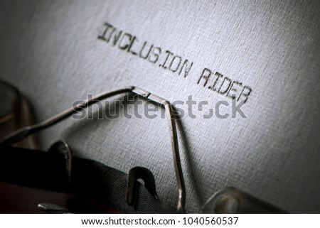 closeup of an old typewriter and the text inclusion rider typewritten with it in a paper, with a slight vignette added