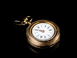 Closeup of an old, used golden pocket watch on a black reflective surface