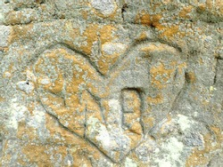 closeup of an old weathered rock with heart names and letters inscriptions carved in it as symbol of love