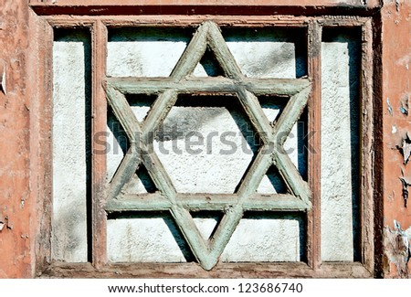 Closeup of an old wooden Star of David into a painted wooden frame of window placed on textured colorful plaster background.