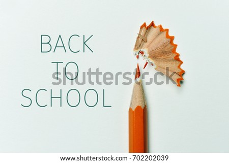 closeup of an orange pencil crayon freshly sharpened, fan-shaped shavings and the text back to school on an off-white background
