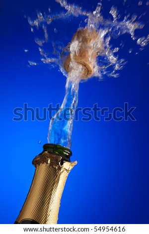 closeup of an uncorked champagne bottle with cork flying away on the liquid