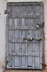 Closeup of ancient rusty iron gate with padlock
