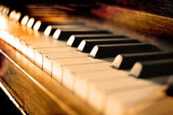 Closeup of antique piano keys and wood grain with sepia tone
