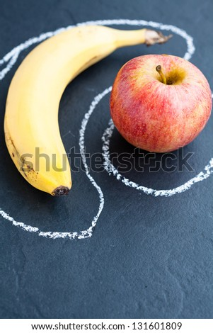 Closeup of apple and banana inside chalk outlines on dark background