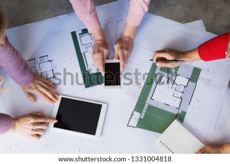 Closeup of architects working with drawings at desk. Drawings, tablet computer and smartphone lying on table. House design and architecture concept. Top view. #1331004818
