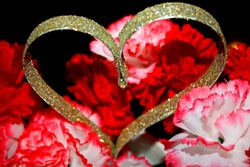 Closeup of artificial pink, red, and white carnations surrounding a gold, glittery heart