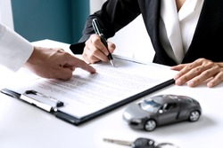 Closeup of Asian female signing car insurance document or lease paper contract or agreement. Buying or selling new or used vehicle with car keys on table.