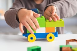 Closeup of asian kid's hand playing plastic  blocks, puzzle. Concept of education and development.
