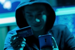 closeup of Asian male hacker fraudulently use credit card for payment